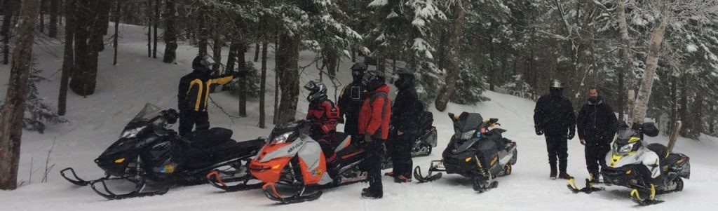 A group of riders with their snowmobiles on the Chittenden Dammers trails